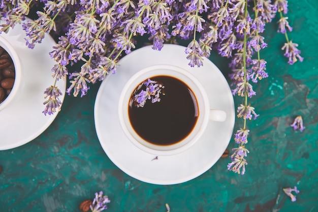 Café, Grain De Café Dans Des Tasses Et Fleur De Lavande Sur Table Verte D'en Haut. Bonjour Concept. Bureau De Travail De Femme. Petit Déjeuner Confortable. Maquette. Style Plat Photo Premium