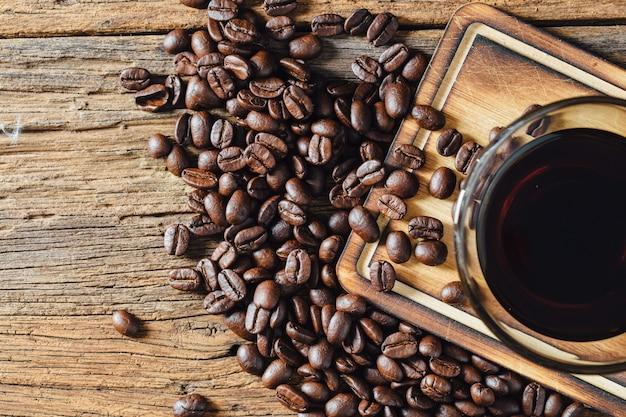 Café et grains de café sur une table en bois Photo Premium