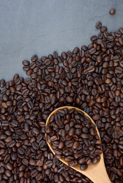 Café en grains avec fond de cuillère à café avec espace. Photo Premium