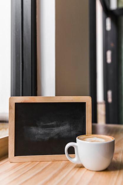Café latte avec ardoise noire sur le bureau en bois Photo gratuit