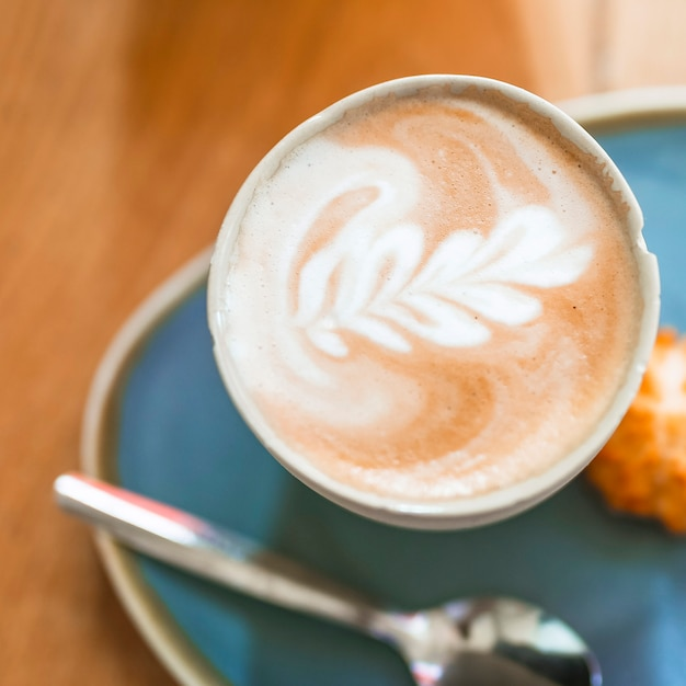 Café latte art cappuccino en mousse sur une table en bois Photo gratuit