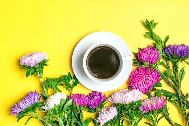 Café noir americano dans la tasse blanche et fleurs asters sur fond jaune plat poser Photo Premium