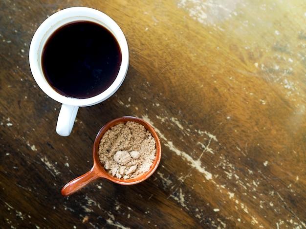 Café noir ou café americano servi avec du sucre de brawn sur une table en bois de style vintage Photo Premium