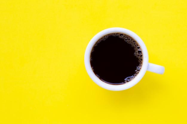 Café noir chaud sur jaune. Photo Premium