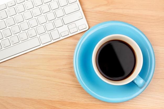 Café noir dans une tasse bleue sur une table en bois marron Photo Premium