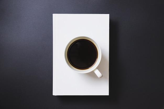 Café noir dans une tasse à café blanche posée sur des livres blancs sur fond noir Photo Premium