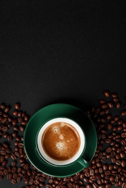 Café noir fort dans une tasse de couleur émeraude sur un fond noir mat Photo Premium