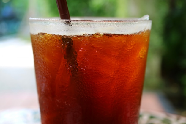 Café noir glacé fermé en verre transparent avec condensation, arrière-plan flou Photo Premium