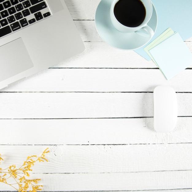 Café et notes autocollantes près d'un ordinateur portable et d'une brindille Photo gratuit