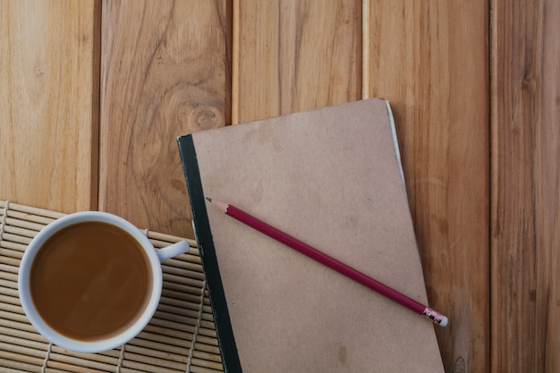 Café placé à côté du livre sur le plancher de bois brun. Photo gratuit