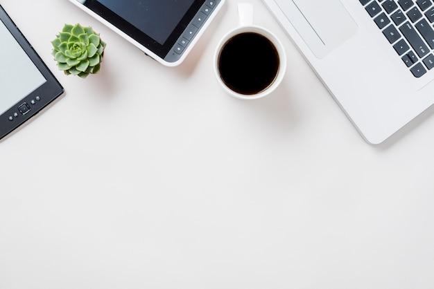 Café Et Plantes Près D'un Ordinateur Portable Et De Livres électroniques Photo gratuit