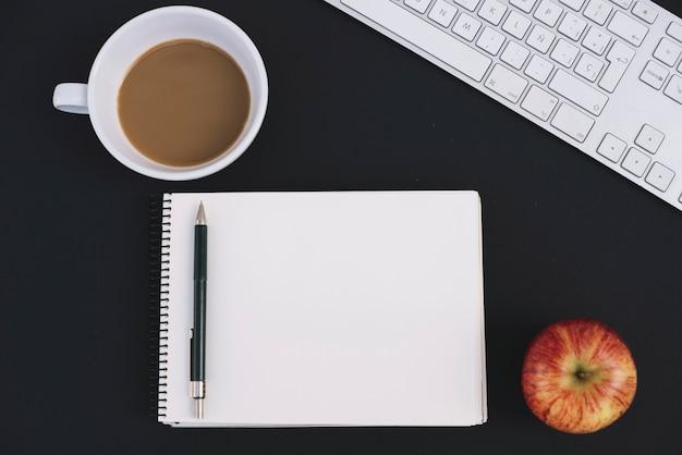 Café et pomme près de carnet et clavier Photo gratuit