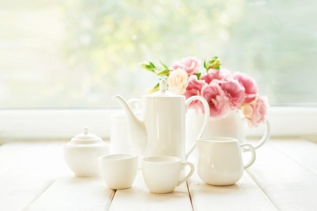 Café posé à côté d'un vase de fleurs sur une table contre une fenêtre Photo Premium