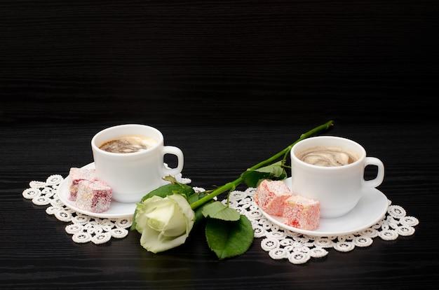 Café pour deux avec des bonbons orientaux, une rose blanche sur un fond noir Photo Premium