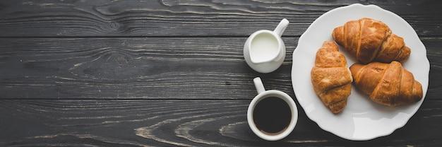 Café et produits laitiers près de la plaque avec des croissants Photo gratuit