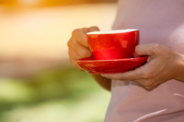 Café tasse rouge mis sur la main le matin sur la verdure floue Photo Premium