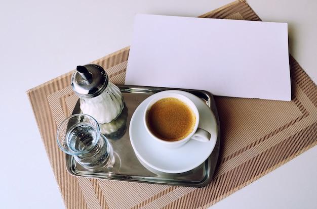 Café, un verre d'eau et du sucre sur un plateau en fer. Photo Premium