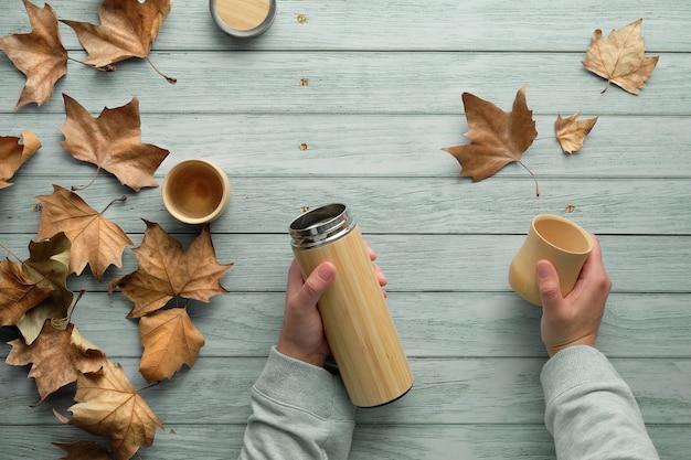 Café Zéro Déchet Dans Des Tasses En Bambou De Flacon En Métal Isolant écologique En Automne. Mains Tenant Le Flacon Et La Tasse. Photo Premium
