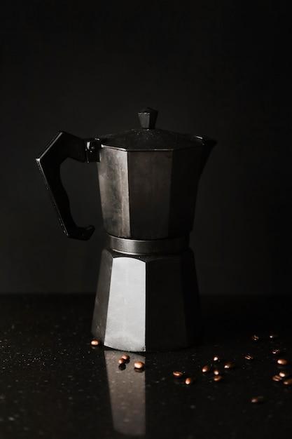 Cafetière avec grains de café sur fond noir Photo gratuit