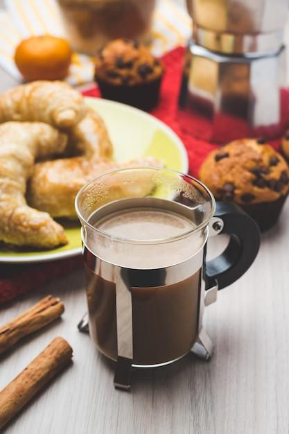 Cafetière, muffins, croissants et tasse de café Photo Premium