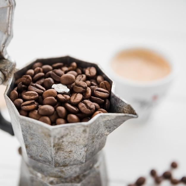Cafetière pleine de grains de café Photo gratuit