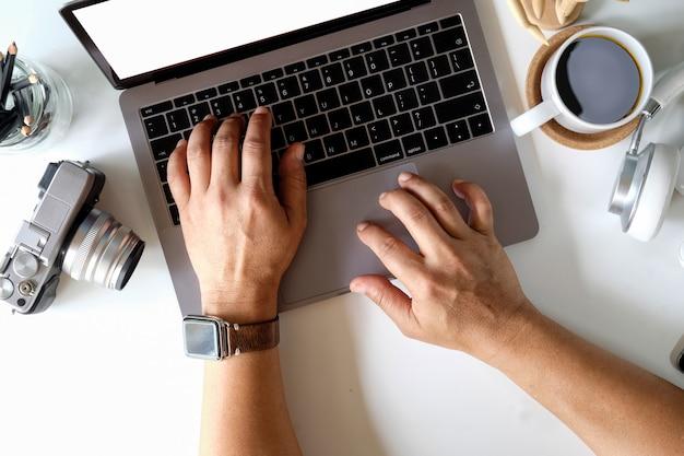 Cagoule masculine travaillant avec un ordinateur portable Photo Premium