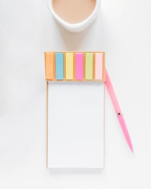 Cahier avec des autocollants près de la tasse à café et stylo Photo gratuit
