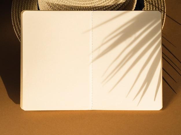 Cahier blanc sur un chapeau et une ombre de feuilles de palmier Photo gratuit