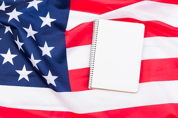 Cahier blanc sur drapeau américain Photo gratuit