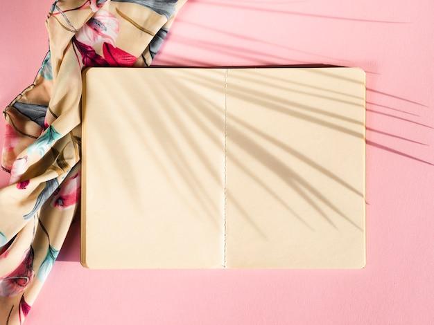 Cahier Blanc Sur Fond Rose Avec Une Ombre De Palme Photo gratuit