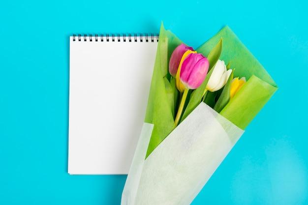 Cahier blanc et tulipes colorées sur fond bleu Photo Premium