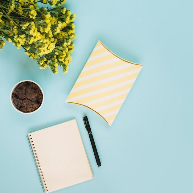Cahier et boite près des muffins et des fleurs Photo gratuit