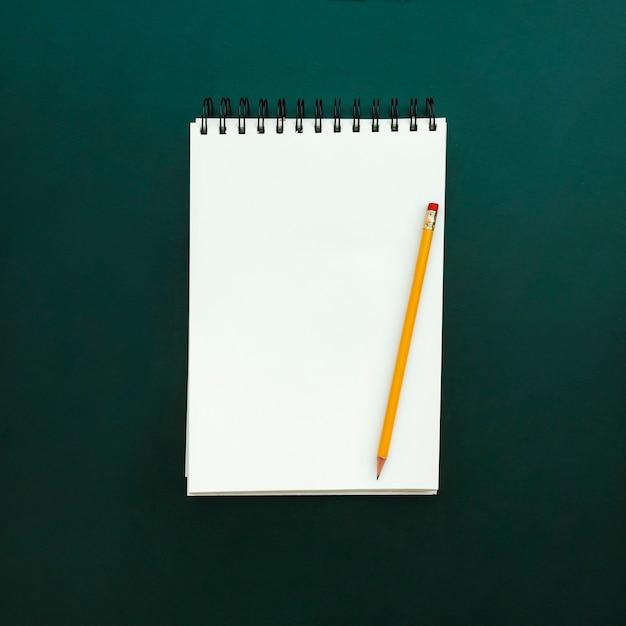 Cahier avec un crayon sur ardoise verte retour à l'école Photo gratuit