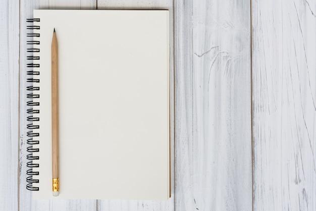 Cahier et crayon brun sur fond de table en bois Photo Premium