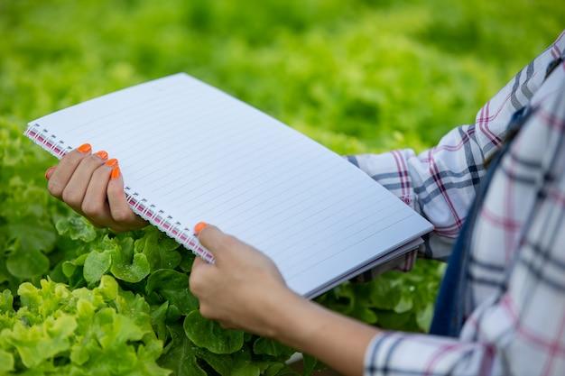 Un cahier entre les mains d'une jeune femme dans la pépinière. Photo gratuit