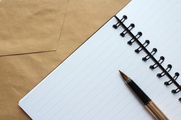 Un Cahier Avec Des Feuilles Propres, Une Enveloppe Et Un Stylo Doré Sur La Table Photo Premium