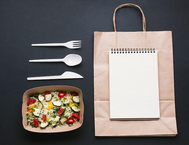 Cahier de notes plat sur maquette de sac en papier Photo gratuit