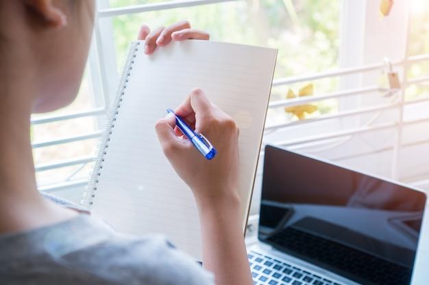 Cahier de notes pour les étudiants asiatiques tout en apprenant l'étude et l'écriture en ligne pour planifier le travail Photo Premium