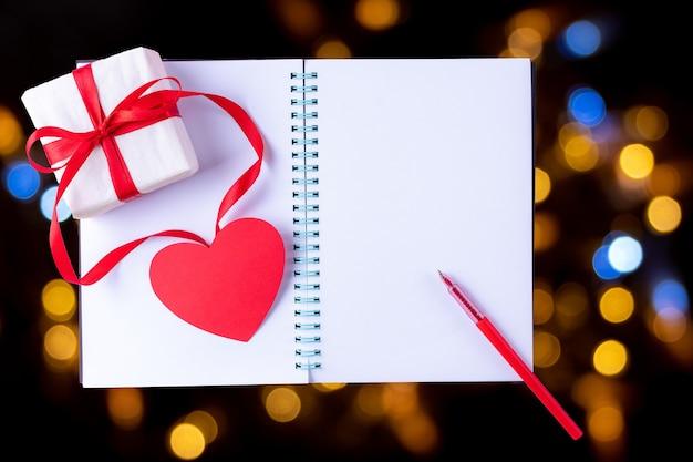 Cahier Ouvert Blanc Blanc, Stylo Rouge, Boîte-cadeau Avec Ruban Rouge Et Forme De Coeur En Papier Rose Photo Premium