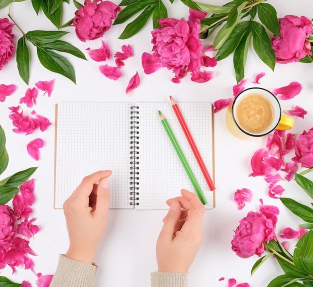 Cahier ouvert dans une cage et deux mains féminines, une tasse jaune avec du café sur un fond blanc Photo Premium