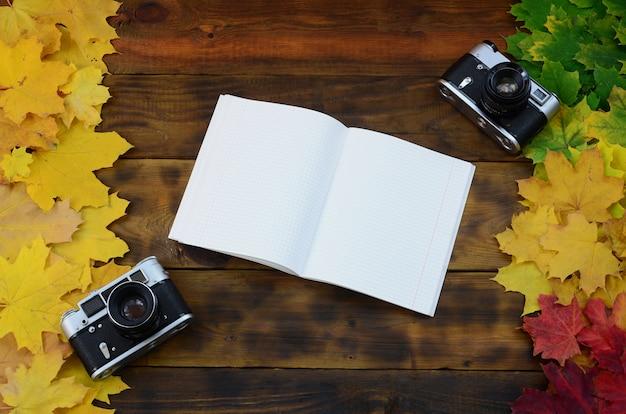 Un cahier ouvert et deux vieilles caméras Photo Premium