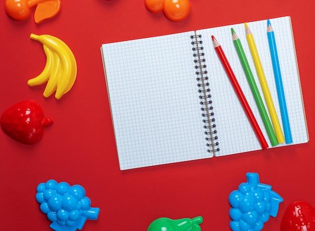 Cahier ouvert avec des draps blancs vides et des crayons en bois multicolores Photo Premium