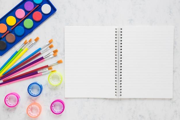 Cahier ouvert avec fournitures de peinture Photo gratuit