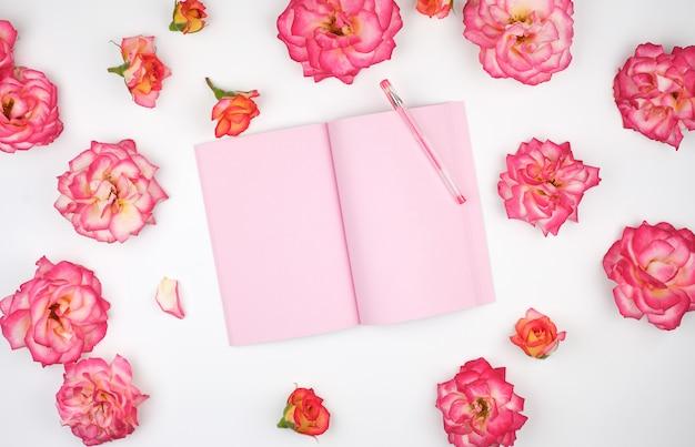 Cahier ouvert avec des pages blanches roses et des pétales de roses roses Photo Premium