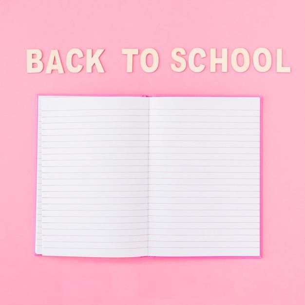 Cahier ouvert près de l'écriture de l'école Photo gratuit