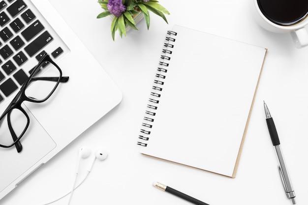 Un cahier avec une page blanche se trouve sur la table de bureau blanche avec des fournitures. vue de dessus, plat poser. Photo Premium