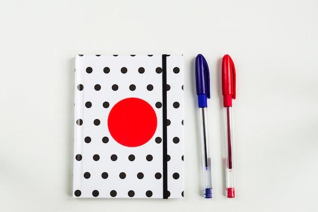 Cahier à pois noir et blanc avec un cercle rouge sur la couverture et des crayons bleus et rouges sur le tableau blanc. vue de dessus, pose à plat minimale Photo Premium