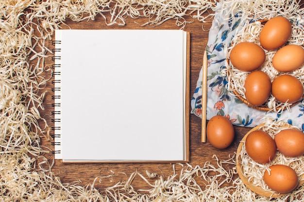 Cahier près d'oeufs de poule dans des bols sur un matériau fleuri entre les guirlandes à bord Photo gratuit
