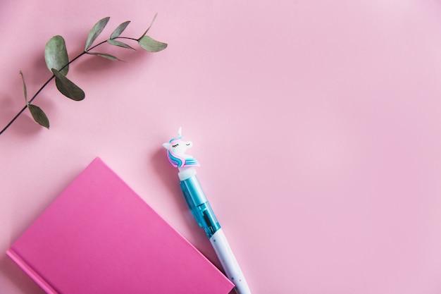 Cahier rose pour les notes, stylo licorne drôle et feuilles d'eucalyptus vert sur fond pastel rose. lay plat. vue de dessus. espace de copie Photo Premium