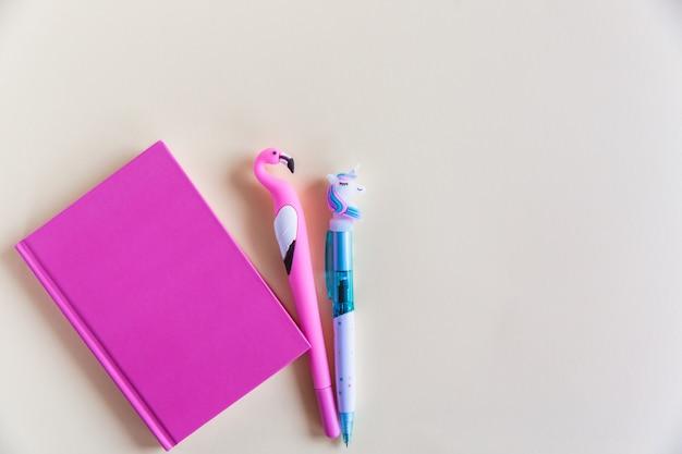 Cahier Rose Pour Notes, Stylos Rigolotes Licorne Et Flamants Sur Fond Jaune Pastel. Lay Plat. Vue De Dessus. Espace De Copie Photo Premium